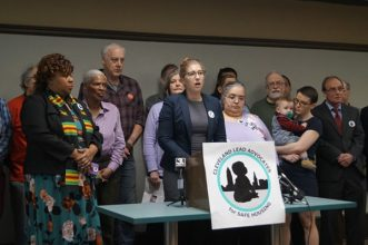 Rebecca Maurer, surrounded by members of Cleveland Lead Advocates for Safe Housing, speaking from a podium with the banner featuring the logo of Cleveland Lead Advocates and Safe Housing.