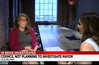 Rebecca Maurer seated at conference table speaking to a female reporter with a white chyron and black text saying 19 News Investigates Council Not Planning to Invesigate Mayor Cleveland