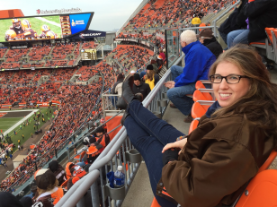 Rebecca Maurer, woman with long brown hair wearing glasses, brown jacket, jeans and boots, sits with her feet on the railing in the forefront overlooking a Cleveland Browns game at the Brown's stadium surrounded by other fans in the seats.