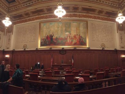 The chambers of Cleveland City Council which take place in a ornate room with dark mahogany wood panelling and desks and red leather chairs all facing a wall that has intricate gold details and a painting above a small wood desk. Several people are seen milling about.