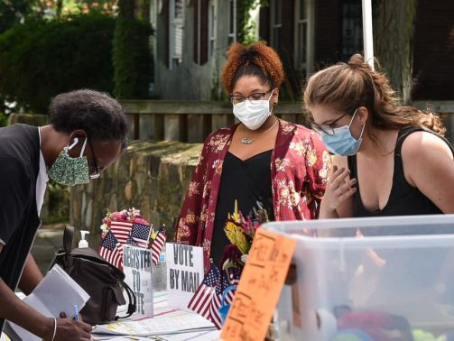 Outdoor voter registration with one person leaning over a table to fill out a form and two women, including Rebecca Maurer, helping with voter registration sign up in a Cleveland Ward 12 neighborhood.